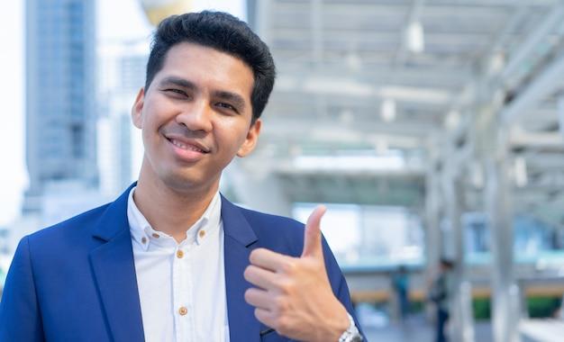 Empresário latino mostra o gesto com a mão polegar para cima (bom sinal) no exterior edifício cidade fundo