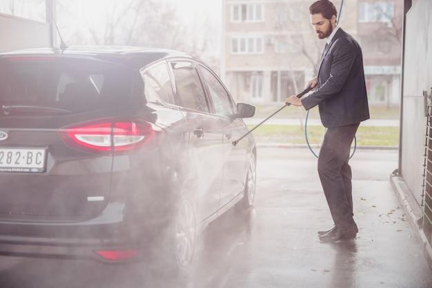 Empresário, lavando o carro na lavagem de carros. expressão facial séria.