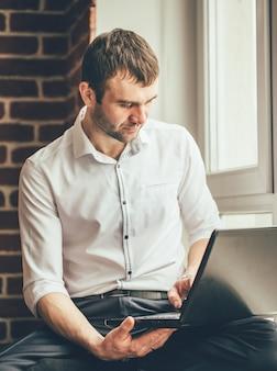 Empresário lê correspondência comercial em seu laptop perto da janela do escritório