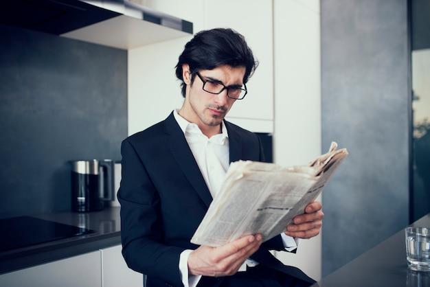 Empresário lê jornal em sua casa moderna