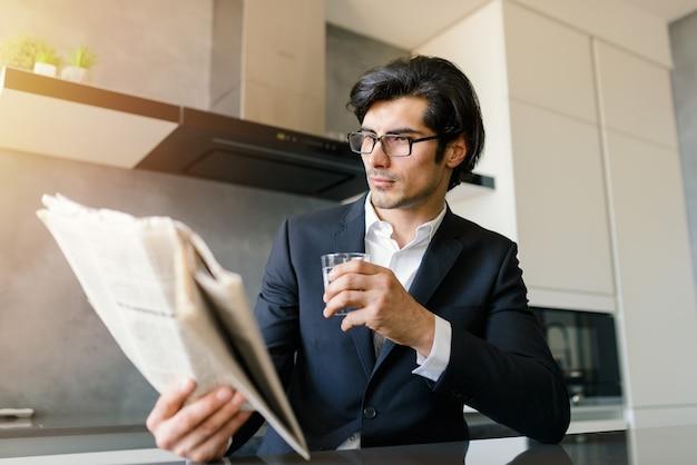 Empresário lê notícias de jornal enquanto toma um café em casa