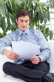 Empresário lendo documentos em um sofá