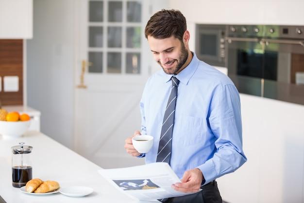 Empresário lendo jornal enquanto bebia café