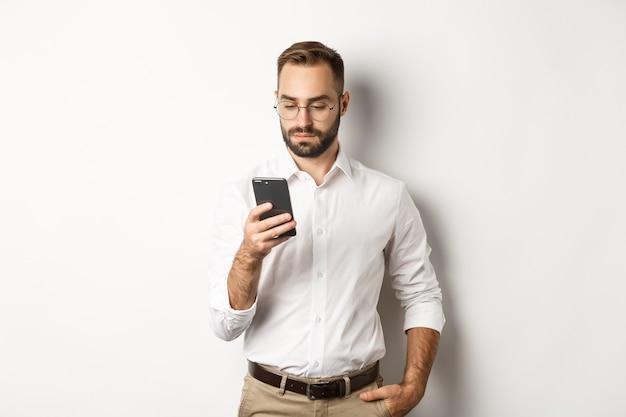 Empresário lendo mensagem no telefone, em pé.
