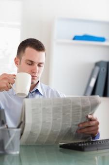 Empresário lendo o jornal e tomando um café