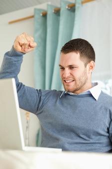 Empresário levantando o punho após o sucesso em seu escritório de casa