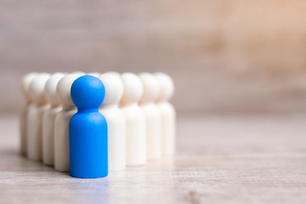 Empresário líder azul com multidão de homens de madeira. liderança, negócios, equipe, trabalho em equipe e conceito de gestão de recursos humanos