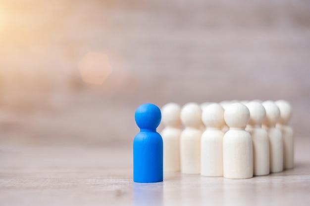Empresário líder azul com multidão de homens de madeira. liderança, negócios, equipe, trabalho em equipe e gestão de recursos humanos