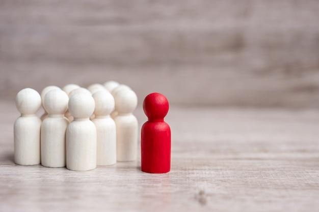 Empresário líder vermelho com multidão de homens de madeira. liderança, negócios, equipe, trabalho em equipe e conceito de gestão de recursos humanos