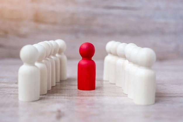 Empresário líder vermelho com multidão de homens de madeira. liderança, negócios, equipe, trabalho em equipe e gestão de recursos humanos