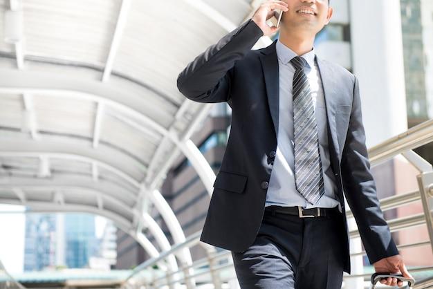 Empresário ligando no celular enquanto puxa bagagem e caminha