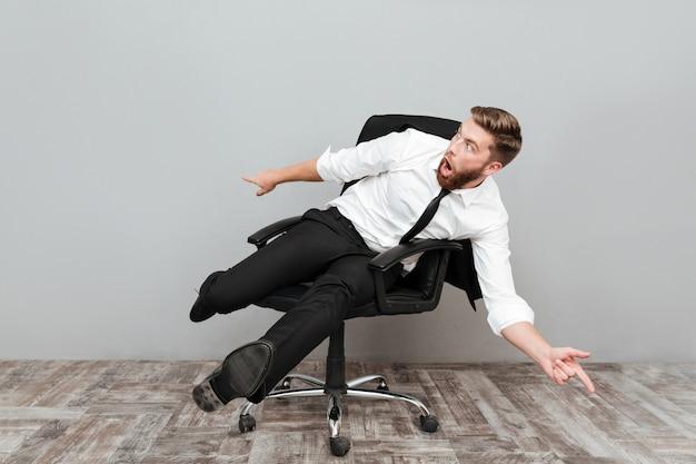 Empresário louco engraçado se divertindo enquanto está sentado na cadeira do escritório