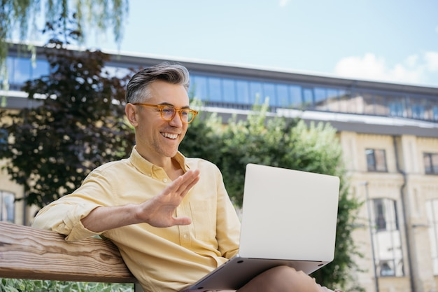 Empresário maduro bonito tendo videoconferência. streaming de vídeo online do blogger