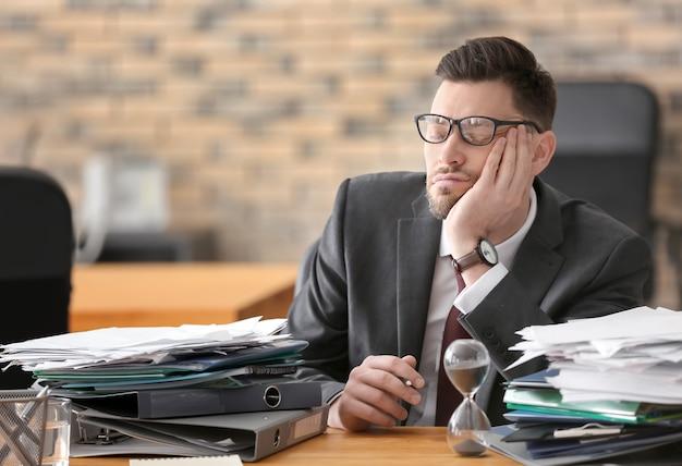 Empresário maduro cansado à mesa no escritório. conceito de gerenciamento de tempo