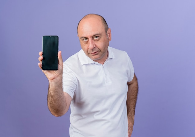 Empresário maduro casual mostrando o telefone celular e olhando para a câmera e mantendo a mão na cintura isolada em um fundo roxo com espaço de cópia