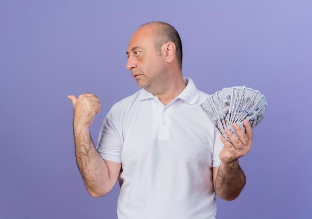 Empresário maduro casual segurando dinheiro virando a cabeça para o lado e apontando para trás, isolado em um fundo roxo com espaço de cópia