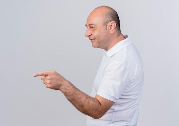 Empresário maduro casual sorridente em pé em vista de perfil, olhando e apontando em linha reta, isolado no fundo branco