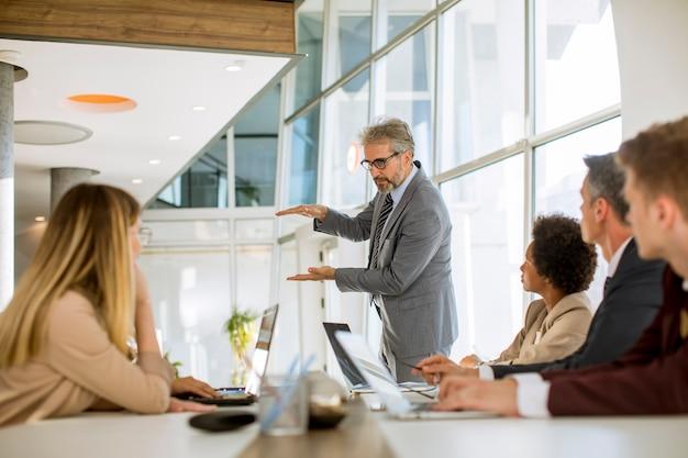Empresário maduro, explicando a estratégia para o grupo de pessoas de negócios multiétnico enquanto trabalhava em novo projeto