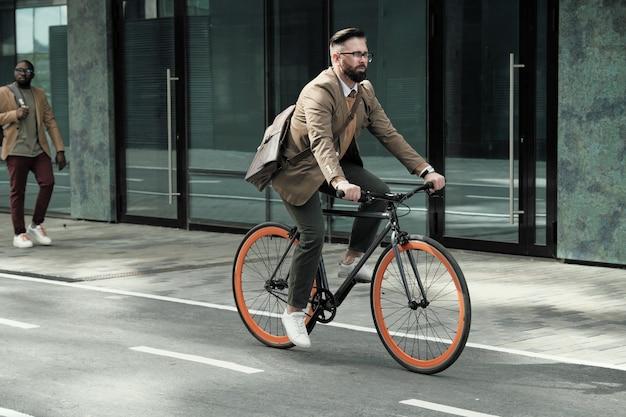 Empresário maduro indo para o trabalho de bicicleta pelas ruas da cidade