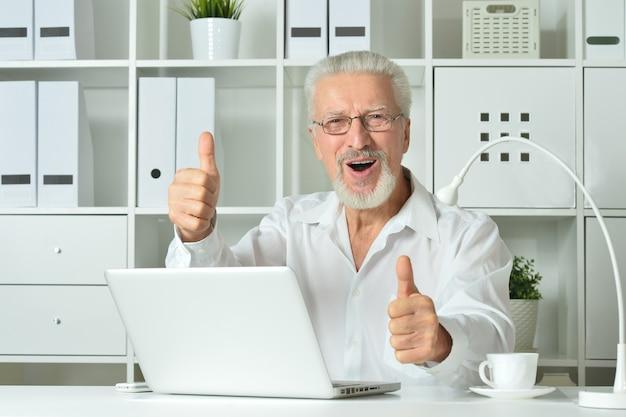 Empresário maduro trabalhando com laptop no escritório com polegares para cima