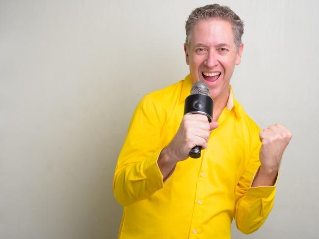 Empresário maduro vestindo camisa amarela e branca