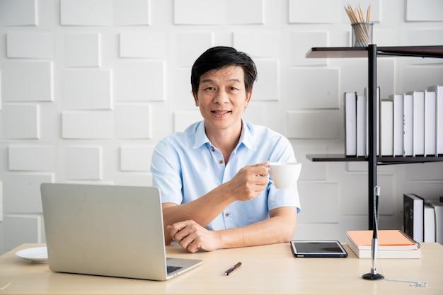Empresário mais velho asiático 'no escritório de manhã