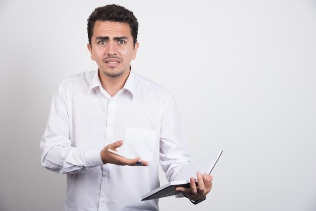 Empresário maluco, apontando para o caderno em fundo branco.