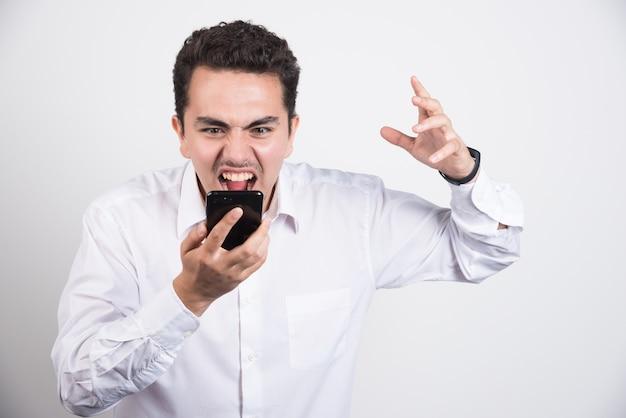 Empresário maluco, gritando com o celular em fundo branco.