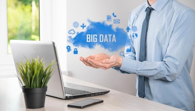 Empresário mantém a inscrição, a palavra big data. cadeado, cérebro, homem, planeta, gráfico, lupa, engrenagens, nuvem, grade, documento, carta, ícone do telefone.
