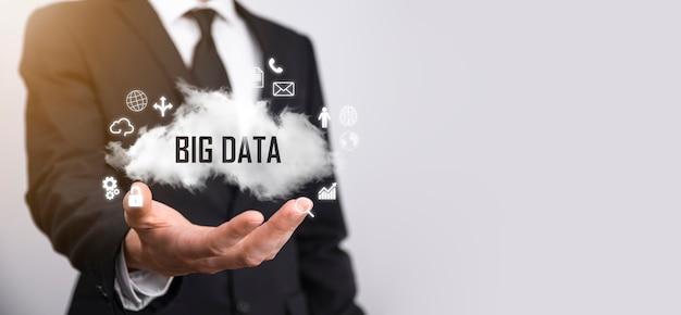 Empresário mantém a inscrição, palavra big data. cadeado, cérebro, homem, planeta, gráfico, lupa, engrenagens, nuvem, grade, documento, carta, ícone do telefone.