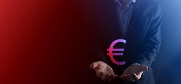 Empresário mantém ícones de moeda de dinheiro eur ou euro em fundo de tom escuro ... conceito de dinheiro crescente para finanças e investimento empresarial. Foto Premium