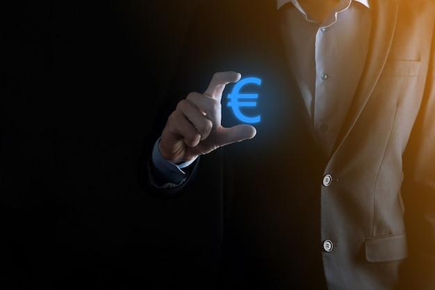 Empresário mantém ícones de moeda de dinheiro eur ou euro na parede de tom escuro ... conceito de dinheiro crescente para finanças e investimento empresarial.