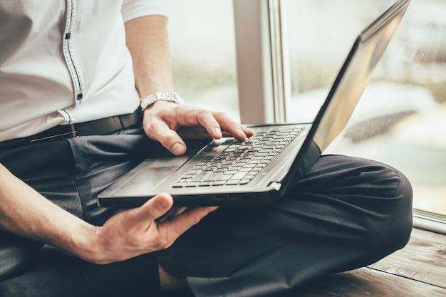 Empresário mantém um laptop em suas pernas e trabalha atrás dele na janela durante o dia na casa