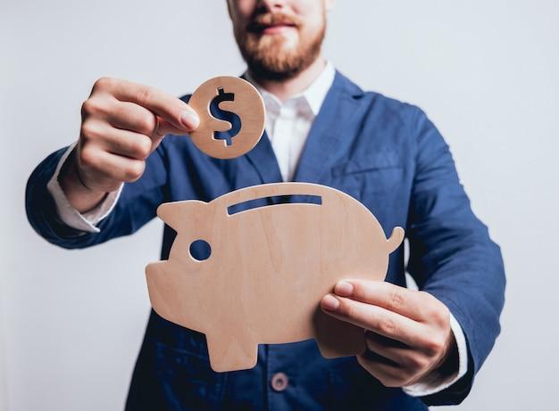 Empresário mantém uma moeda sob o porquinho de madeira.