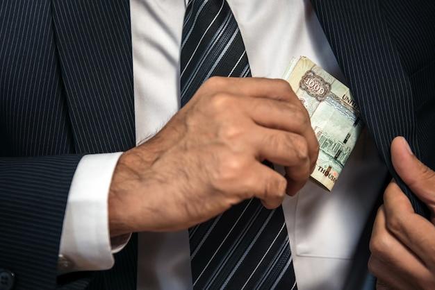 Empresário, mantendo o dinheiro de notas nos emirados árabes unidos no bolso do terno