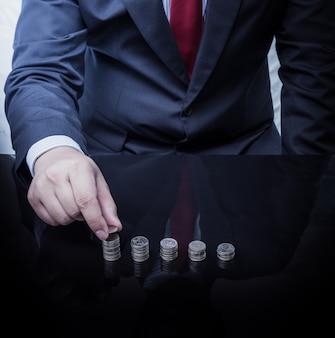 Empresário mão coloca moedas para pilha de moedas