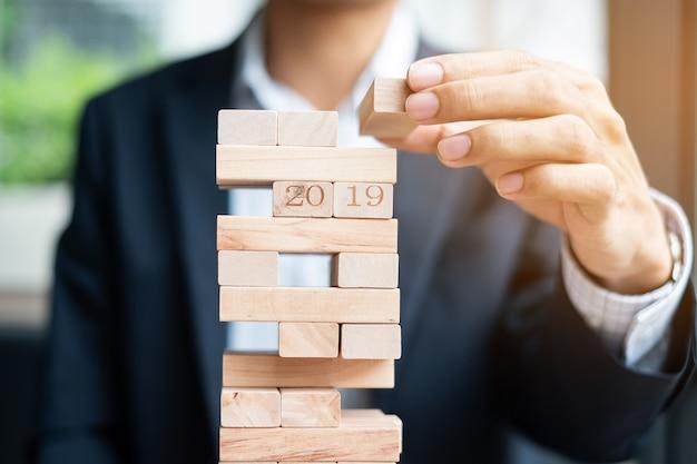 Empresário mão colocando ou puxando o bloco de madeira na torre