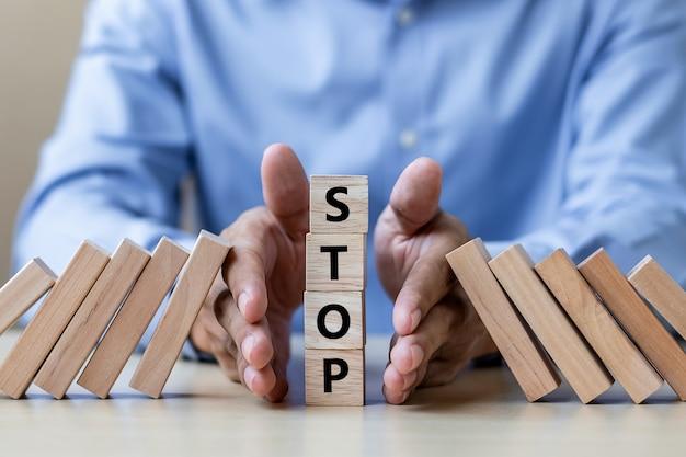 Empresário mão parando queda de blocos de madeira ou dominós