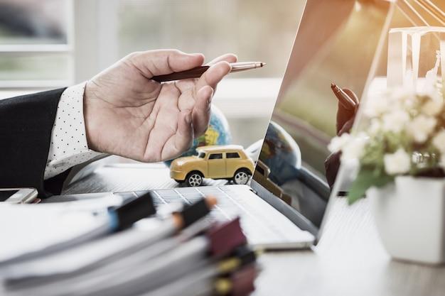 Empresário mãos segurando a caneta para trabalhar em pilhas de arquivos de papel pesquisando o relatório de informações