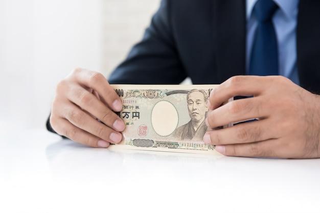 Empresário mãos segurando dinheiro, moeda iene japonês, na mesa