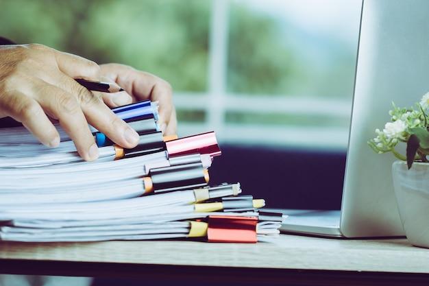 Empresário mãos segurando o lápis para trabalhar em pilhas de arquivos de papel pesquisando