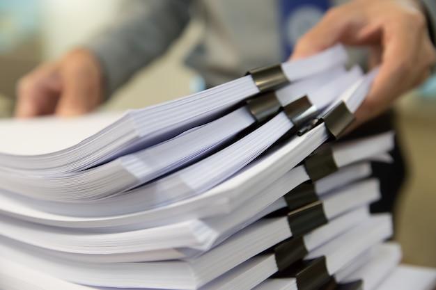 Empresário mãos trabalhando em pilhas de arquivos em papel para pesquisar informações no escritório de mesa de trabalho