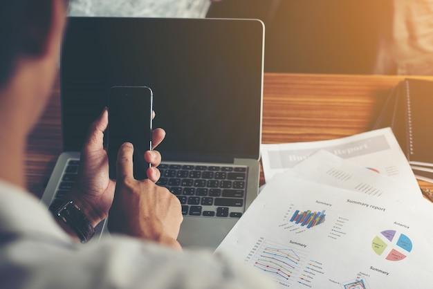Empresário mãos usando telefone celular com o relatório financeiro no off