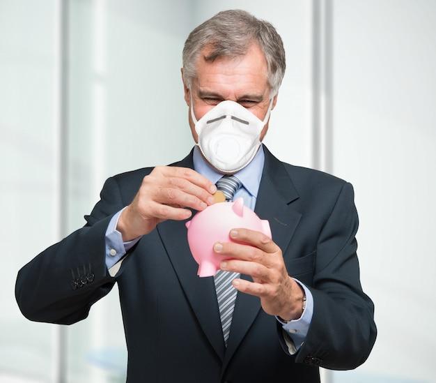 Empresário mascarado colocando dinheiro em um cofrinho