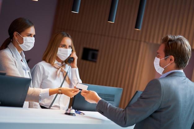 Empresário mascarado na recepção de um hotel fazendo check-in