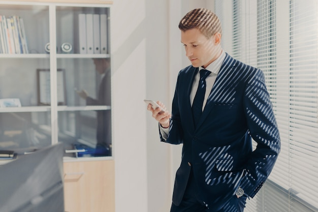 Empresário masculino bonito, lê a mensagem de texto