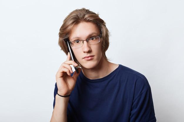 Empresário masculino de boa aparência, usando óculos elegantes, telefonando para o parceiro