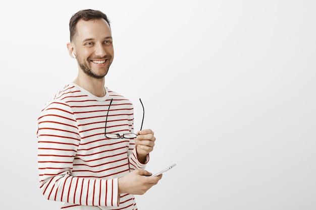 Empresário masculino de sucesso positivo, tirando os óculos, olhando para o lado e sorrindo amigavelmente, escolhendo música para ouvir no smartphone, usando fones de ouvido sem fio