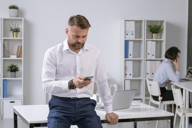 Empresário masculino maduro ou empregador enviando mensagens de texto ou rolando no smartphone com um jovem colega sentado ao lado de um laptop