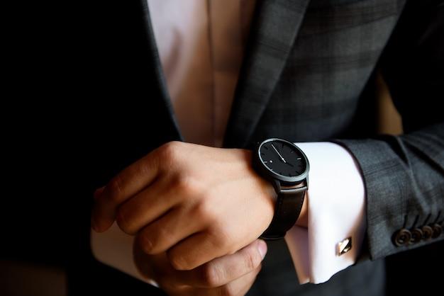 Empresário masculino se veste e ajusta o relógio, preparando-se para uma reunião.
